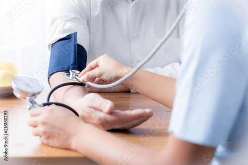 Close-up of nurse with stethoscope checking blood pressure of senior person - 216160293