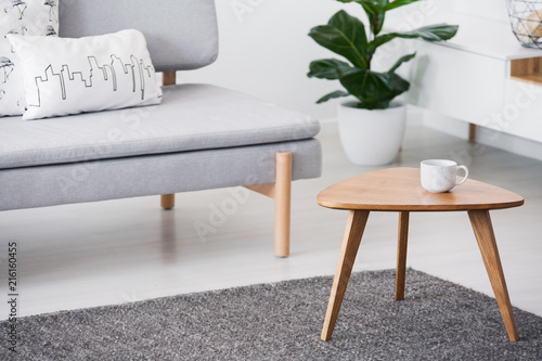 Cup on a wooden coffee table and blurry foreground with graphic pillows on a gray sofa in a white living room interior - 216160455