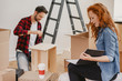 Redhaired woman looking at photobook while furnishing the flat with husband - 216160818