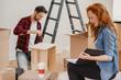 Leinwandbild Motiv Redhaired woman looking at photobook while furnishing the flat with husband