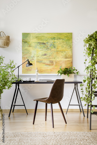 Black desk, industrial lamp and a vintage chair in a white home office interior with an abstract painting and green plants