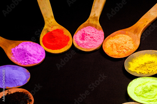 colourful powder paint on black fabric. colourful powder paint in wooden spoon on black fabric in black background with copy space. powder paint is a natural color that humans use.