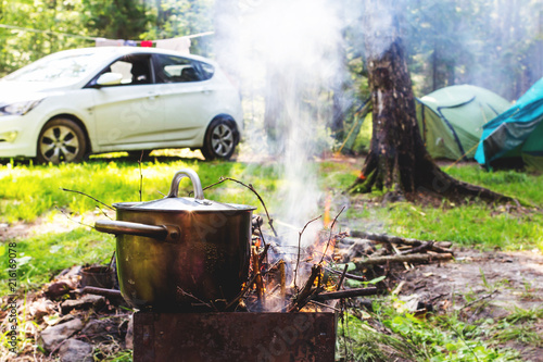 Summer camping in the forest. Hiking pot on the campfire, car and camping tents on background. Concept of a family holiday in nature.