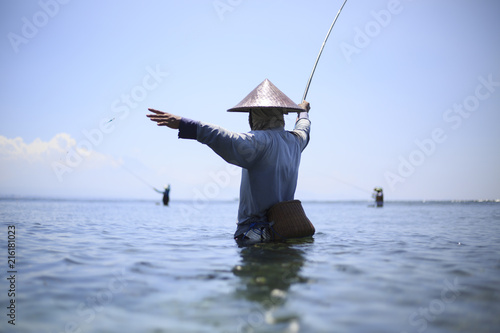 Fotobehang Bali Fisherman is fishing in the sea in Bali in Indonesia
