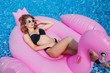 Leinwandbild Motiv A young beautiful girl with a beautiful figure in a black swimsuit and sunglasses is resting and sunbathing in a pool with inflatable flamingos.
