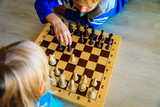 little boy and girl play chess