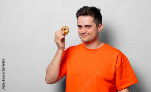 Young handsome man in orange t-shirt with cookie. Studio image on white background