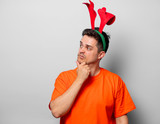 Young handsome man in orange t-shirt with Christmas deer horns. Studio image on white background - 216196632