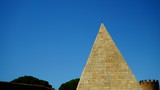 Rome, Italy - July 19, 2018: view of the Cestia pyramid from the street in front with blue sky