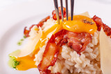 Italian Main Course. Risotto carbonara with egg yolk, Parmesan cheese and bacon white background