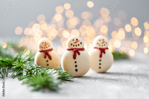 Sweet macaroons in the form of a snowman. Fir branches on a gray background. Merry Christmas card. New year mood