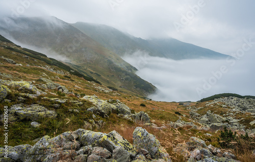 Foggy Mountain Landscape. Grass and Rocks in Foreground.