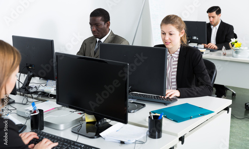 Managers with laptops working in office
