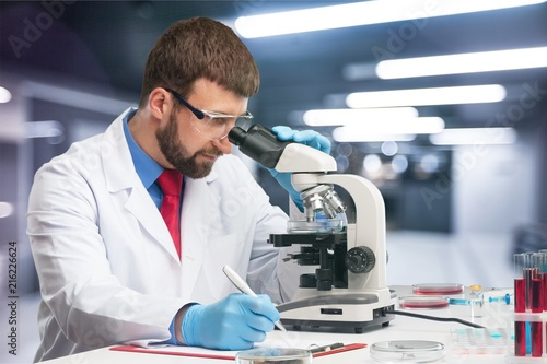 Young male scientist Working with Microscope - 216226624