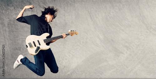 Leinwandbild Motiv Portrait of a Musician Jumping while Playing