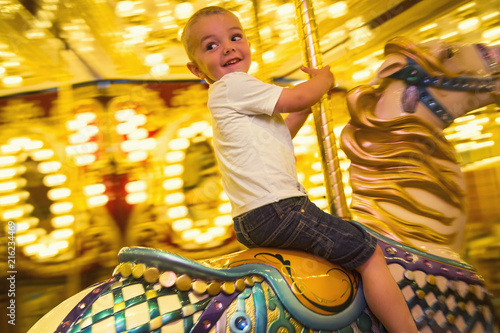 Aluminium Amusementspark Cute little boy having fun riding a carousel at an amusement park or carnival. Happy little boy riding a merry go round carousel with bright lights