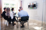 Group Of Diverse Businesspeople Video Conferencing In Boardroom - 216239649
