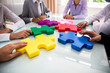 Leinwanddruck Bild - Group Of Businesspeople Solving Jigsaw Puzzle