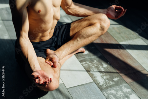 Leinwandbild Motiv yoga instructor. fitness trainer. sport and athletic lifestyle. concentrated serene fit toned and muscular male teacher meditating.