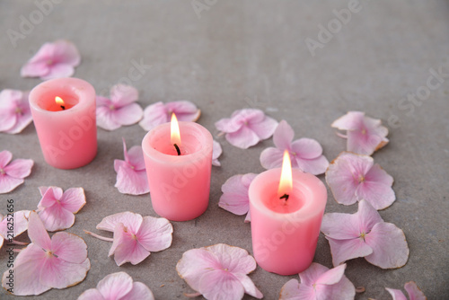 Plexiglas Spa Many Pink hydrangea petals with three candle on gray background