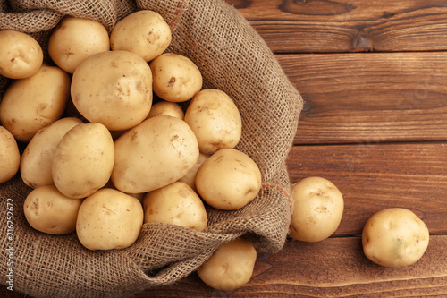 Pile of potatoes lying on wooden boards - 216252672