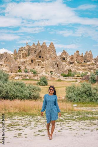 Plexiglas Pool young woman in dress with hat at the fairytale landscape of Cappadocia Kapadokya Turkey