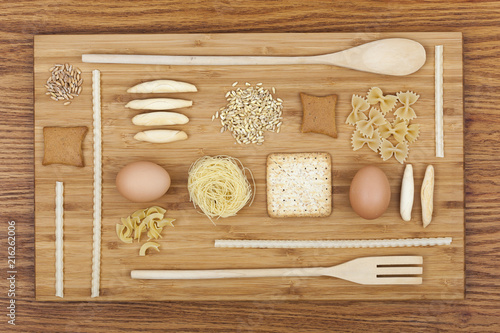 Foto Murales Art composition with pasta, cookies, eggs, wooden kitchen set on wooden cutting board