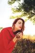 Quadro Mujer pelirroja con camisa roja en el campo en otoño