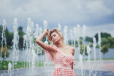 Young beautiful stylish girl walking and posing in dress in city near fountains. Outdoor summer portrait of young woman