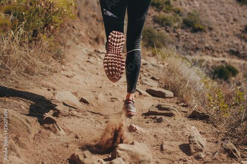 Leinwanddruck Bild Woman runner running on mountain trail