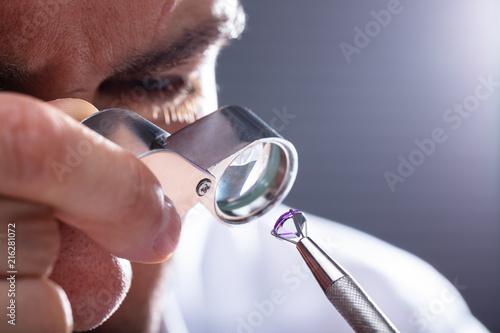Leinwandbild Motiv Jeweler Looking At Diamond Through Magnifying Loupe