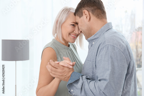 Adorable mature couple dancing together indoors
