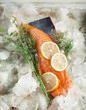 Salmon steak on ice with dill herbs and lemons in a vintage baking sheet, rustic food photography - 216290265