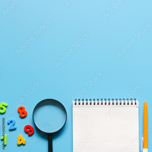 Notebook, pen, magnifier, colorful numbers on blue background.