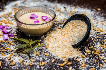 Close up of face pack for Acne and pimples: Oatmeal with water on wooden surface with some Rosa petals. © mirzamlk