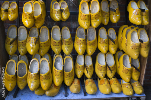 Pairs of yellow wooden shoes in a shop hanging on a wall