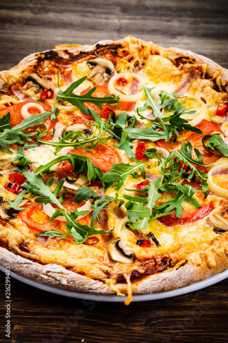 Pizza with ham and vegetables on wooden table  - 216299483