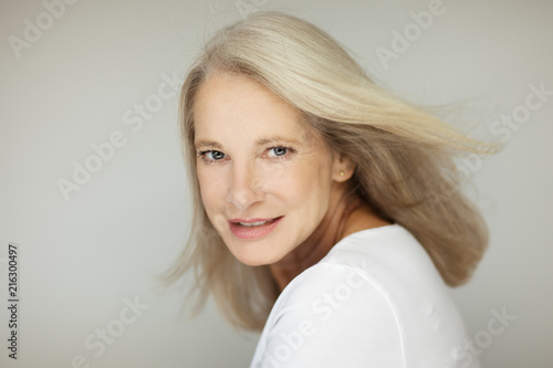 Leinwanddruck Bild stunning beautiful and self confident best aged woman with grey hair smiling into camera, portrait with white background