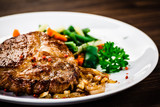 Grilled steak with vegetables on wooden background - 216303431