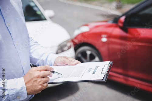 Fototapeta Traffic Accident and insurance concept, Insurance agent working on report form with car accident claim process