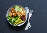 Healthy balanced buddha bowl - spicy couscous with chickpeas, broccoli, green beans and turkey meatballs on dark background, top view. Copy space - 216322624