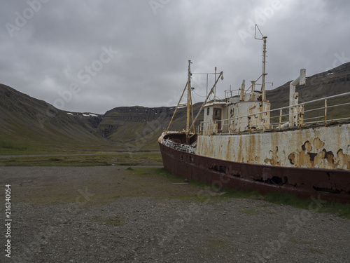 Aluminium Schipbreuk Old abandoned rusty fishing boat ship wreck standing on the sand beach coast in west fjords od Iceland, dramatic gray sky and hills background in Patreksfjordur, Iceland, west fjords,