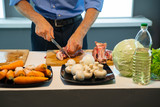 A man cuts meat with a knife on the kitchen table - 216363077