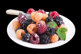 Raspberry and blackberry closeup in white plate with fork