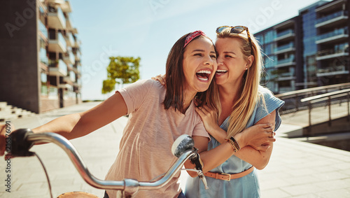 Laughing female friends having fun walking together through the - 216376091
