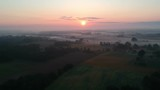 Drone fly above Summer time sunrise and mist in farmland, aerial view - 216381045