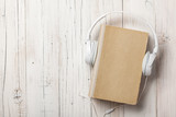 Audiobook concept with old book and headphones