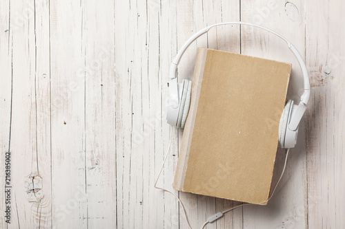Audiobook concept with old book and headphones - 216385002