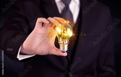 Foto Murales An elegant office worker holding a yellow sparkling light bulb in his hand while working in front of dark blue background concept.