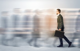 Young businessman with briefcase hurry up on a crowded street with blurred people around
